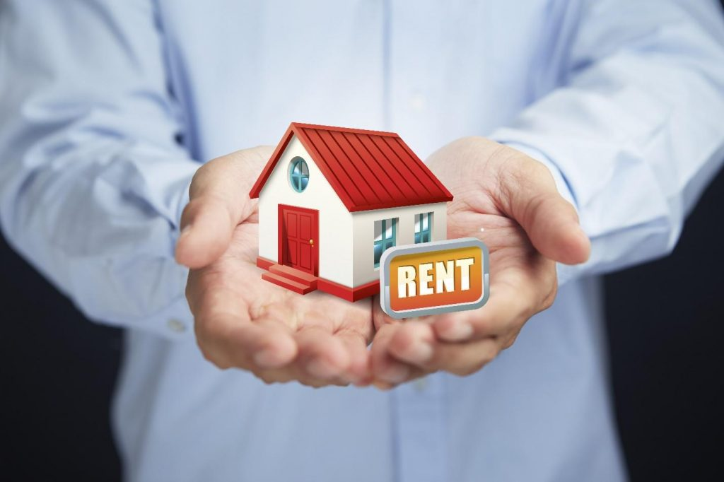 Close up of a person holding a miniature house with a rental sign on it