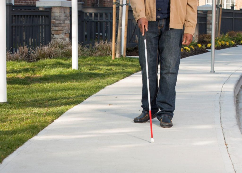 Picture of a man walking down a sidewalk with a cane